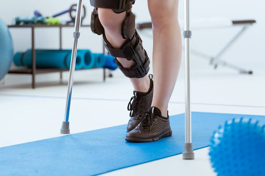 injured-patient-in-a-leg-brace-exercising-on-a-blu-M3S6XEC-1